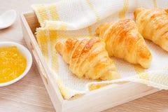在木盘子和果子果酱的新月形面包 库存照片