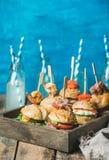 在木盘子和柠檬水的自创汉堡在玻璃瓶 图库摄影