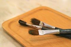 在木盘子的三支画笔在桌上 免版税库存图片