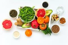 在木盘子的健康食物:水果、蔬菜、种子和绿色在白色背景 库存图片