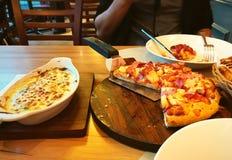 在木盘子的夏威夷平底锅薄饼用被烘烤的菠菜和乳酪 库存图片