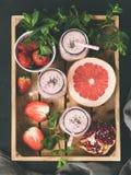 在木盘子的果子和莓果圆滑的人 库存照片