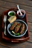 在木盘子的Kebabs用酸果蔓酱 免版税库存图片