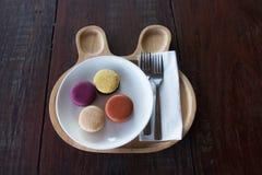 在木盘的五颜六色的macarons与叉子 库存图片