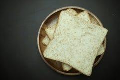 在木盘的全麦面包在黑背景 库存照片