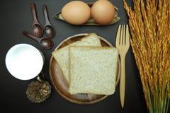 在木盘的全麦面包在黑背景 免版税图库摄影