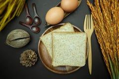 在木盘的全麦面包在黑背景 免版税库存照片