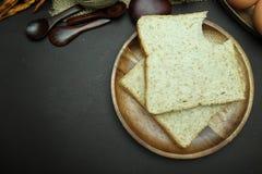 在木盘的全麦面包在黑背景 免版税库存图片