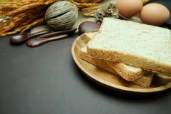 在木盘的全麦面包在黑背景 库存图片