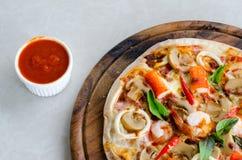 在木盘的西红柿酱和海鲜意大利薄饼切片 免版税库存图片