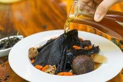 在木盘的黑鸡汤 库存图片