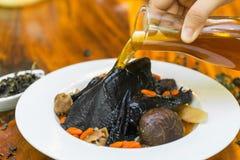 在木盘的黑鸡汤 免版税库存图片