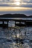 在木码头的剧烈的黑暗的日落在湖在哥特人,瑞典附近的Ingared 库存照片