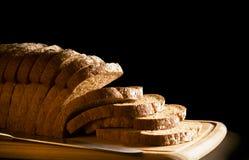 在木砧板的切的棕色大面包 免版税图库摄影