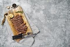 在木砧板的切的牛肉牛后腹肉排 灰色背景,顶视图,文本的空间 免版税库存图片