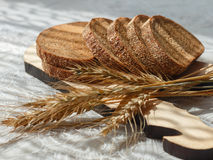 在木砧板的被切的面包和麦子小尖峰 在切片的焦点 免版税库存照片