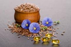在木碗、秀丽花和油的亚麻籽在盖帽 免版税库存图片