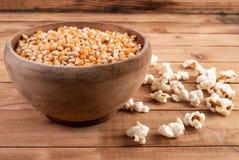 在木碗和流行的玉米花的未加工的玉米种子在桌上 免版税库存图片