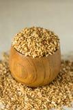 在木碗的亚麻籽有在,在亚麻布,关闭附近的溢出的种子的 库存照片
