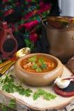 在木碗的传统乌克兰甜菜汤罗宋汤有大蒜小圆面包pampushka的和烘干在土气木桌上的被治疗的猪肚 免版税库存图片
