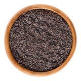 在木碗的地面灰色罂粟种子在白色 免版税图库摄影