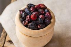 在木碗的干玫瑰果莓果,在亚麻制毛巾,健康概念,自然医学 库存照片