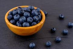 在木碗的成熟蓝莓在黑石桌背景 侧视图 免版税库存图片