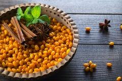 在木碗的新鲜的成熟有机海鼠李莓果用肉桂条、茴香星和薄菏在黑暗的背景 库存照片