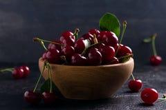在木碗的新鲜的樱桃在黑背景 新鲜的成熟甜樱桃 库存照片