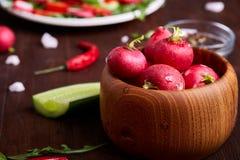 在木碗的新鲜的红色萝卜在有菜、草本和spicies的,顶视图,选择聚焦板材中 免版税图库摄影