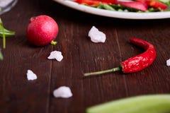 在木碗的新鲜的红色萝卜在有菜、草本和spicies的,顶视图,选择聚焦板材中 免版税库存照片