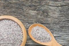 在木碗的未加工的Riceberry米有在自然木头bac的匙子的 库存照片