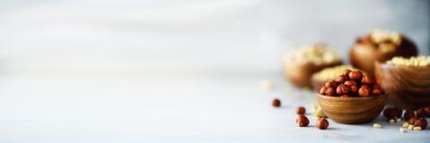 在木碗的榛子 食物混合背景,顶视图,拷贝空间,横幅 坚果的分类-腰果,榛子 免版税库存图片