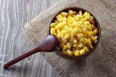 在木碗的玉米在桌上 免版税库存照片