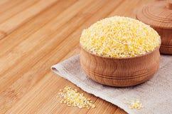 在木碗的玉米渣在棕色竹板,特写镜头 土气样式,健康饮食少量背景 库存照片