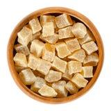 在木碗的糖煮的姜根立方体在白色 免版税库存照片
