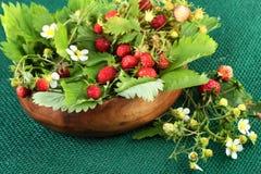 在木碗的野草莓在黄麻织品背景 免版税库存照片