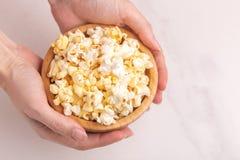 在木碗的鲜美咸玉米花在妇女的手上 免版税图库摄影