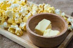 在木碗的黄油用玉米花 库存图片