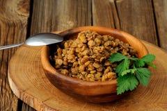 在木碗witn金属匙子的煮熟的扁豆 图库摄影