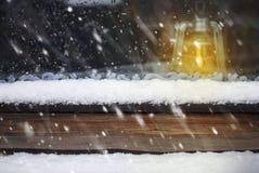 在木窗口和落的雪的油灯 免版税图库摄影