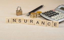 在木立方体的词保险 计算器、笔、硬币和挂锁在桌上 保险和挽救概念 免版税库存图片