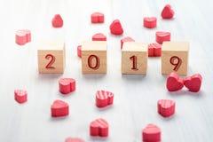 在木立方体的2019个新年与小组在白色的微型红色心脏 图库摄影