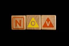 在木立方体的11月在黑背景 免版税库存照片