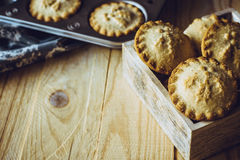 在木箱子和烘烤盘子的肉馅饼在背景中,在厨房用桌上,定调子在葡萄酒样式 库存图片