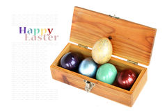 在木箱子的五颜六色的鸡蛋在与样品的白色背景发短信 库存照片