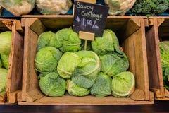 在木箱摊位的新鲜的圆白菜菜在有价格黑板标签的蔬菜水果商 免版税库存照片