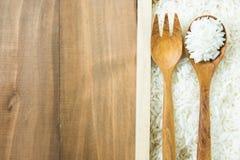 在木箱有棕色木叉子的和匙子的白色未加工的泰国茉莉花米在木桌上 免版税库存图片