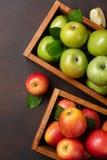 在木箱的成熟红色和绿色苹果在生锈的背景 免版税库存照片