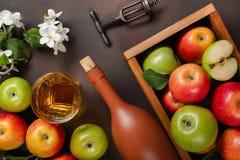 在木箱的成熟红色和绿色苹果有白花、玻璃和瓶分支的在生锈的背景的萍果汁 库存图片
